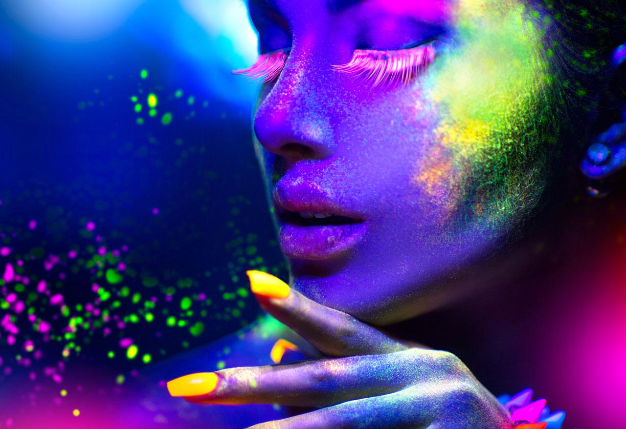 Geschminkte Frau im Schwarzlicht mit bunt fluoreszierendem Makeup
