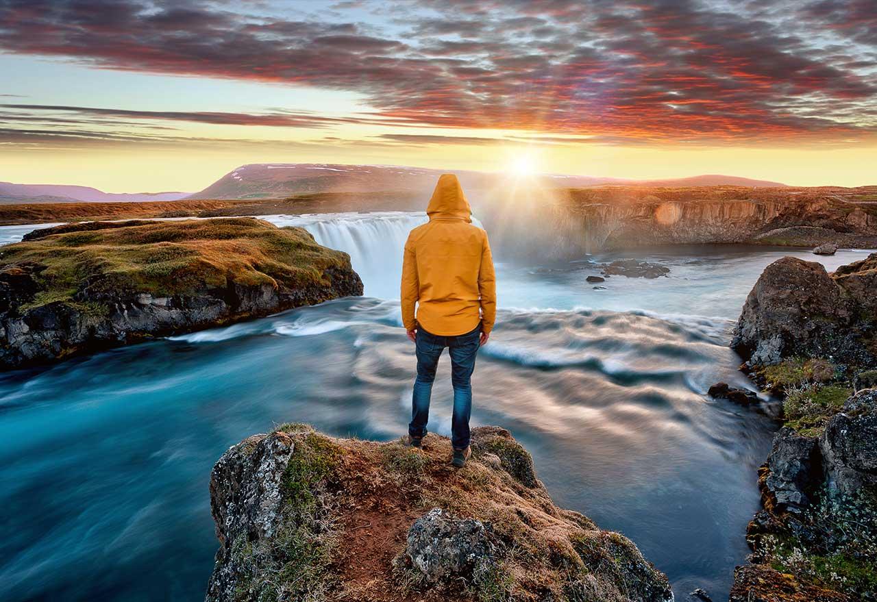 Person in gelbem Regenmantel steht auf einem Berg vor einem Tal mit Wasserfall mit Sonnenuntergang